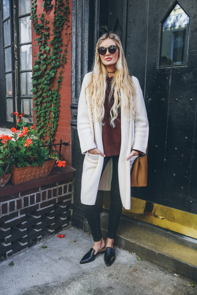 Amber Fillerup Clark debuts a wonderful fall trend here; the long cardigan! Paired with simple jeans and smart leather slip on shoes, this cardigan is cosy, chic, and totally seasonal. We love it!  Sweater/Cardigan: Vince, Jeans: 3×1, Shoes: Schutz.