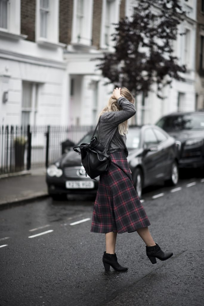 Tiphaine is wearing an edgy plaid skirt with cute black ankle boots and a leather backpack.  Top: Alexander Wang, Skirt: The Fifth Label, Boots: Rag & Bone.