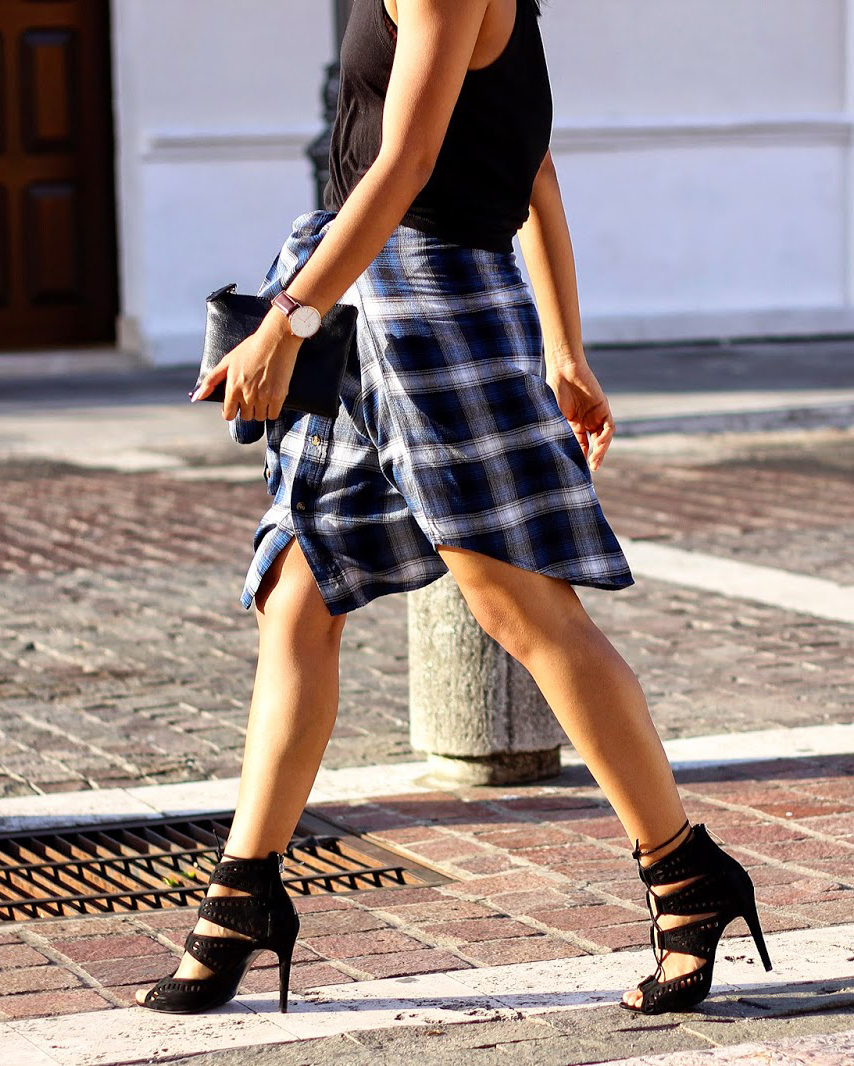 Génesis Serapioi is wearing a plaid shirt worn as a skirt from Thrifted and the tank top and shoes are from Zara