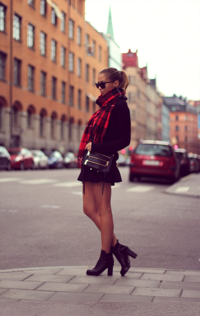 Kenza Zouiten is wearing a skirt from Zara, plaid scarf from Gina Tricot, boots from Acne, bag from Rebecca Minkoff and sunglasses from Prada