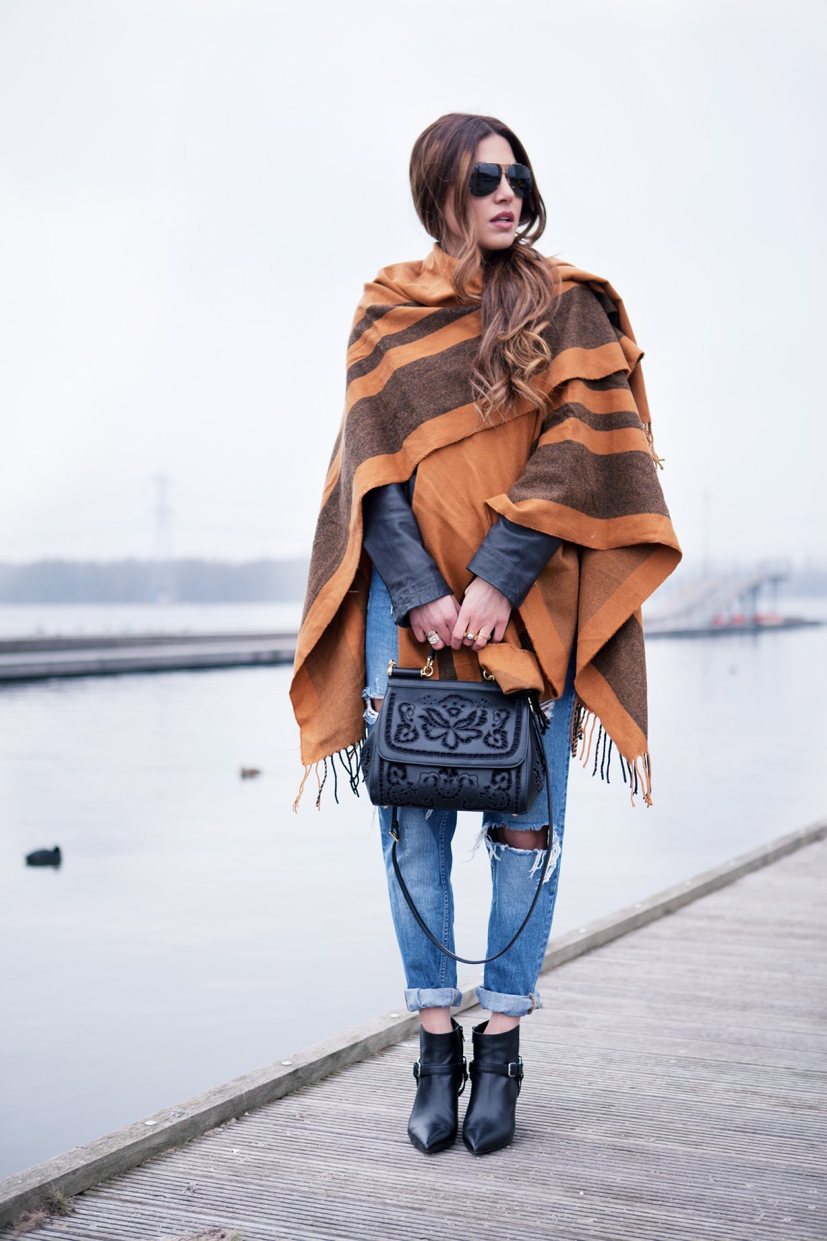 Negin Mirsalehi is wearing a orange and black striped blanket cape from Asos