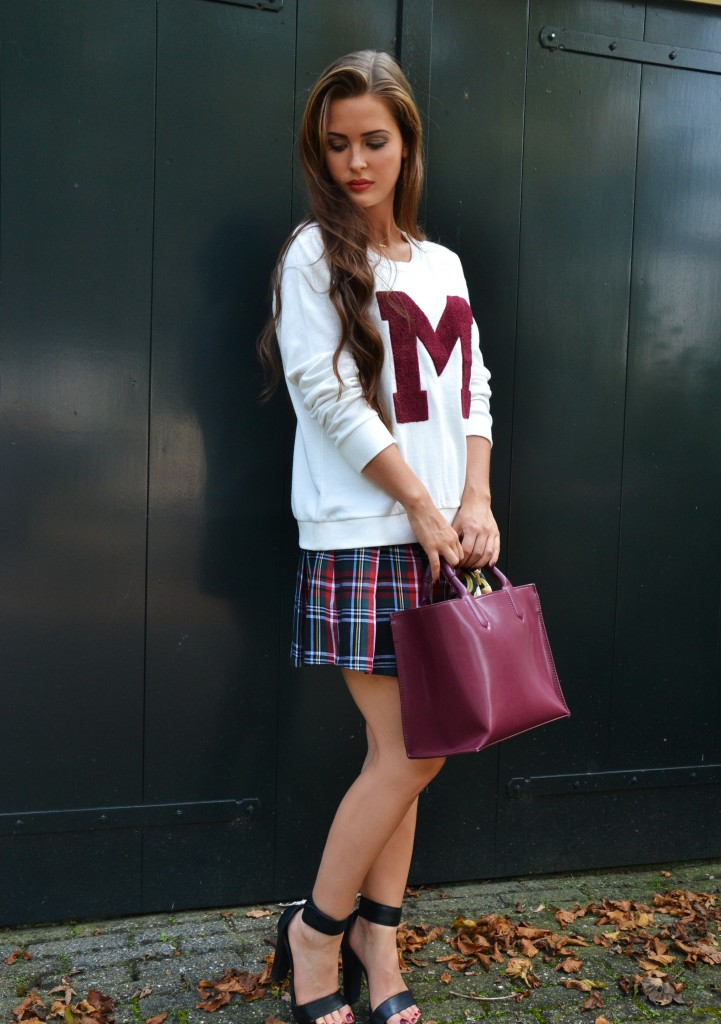 Murielle Van Schaik is wearing a M printed varsity sweatshirt and a plaid pleated skirt from Mango and the platforms are from River Island
