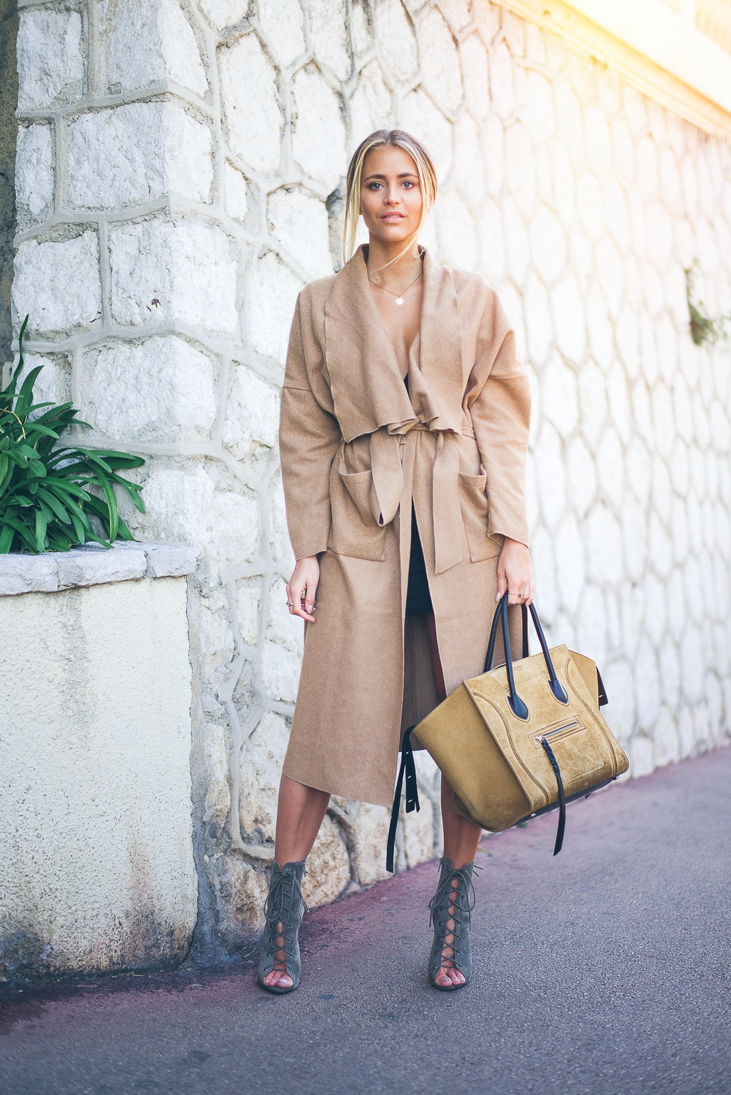 Janni Deler rocks this camel waist tie robe coat by wearing it with classic gladiator sandals and a sand coloured bag. Sticking to a general colour scheme can be very effective, as demonstrated here. Coat: Lookbook Store, Dress: Nly Trend by Janni Delér, Bag: Céline, Shoes: Public Desire.
