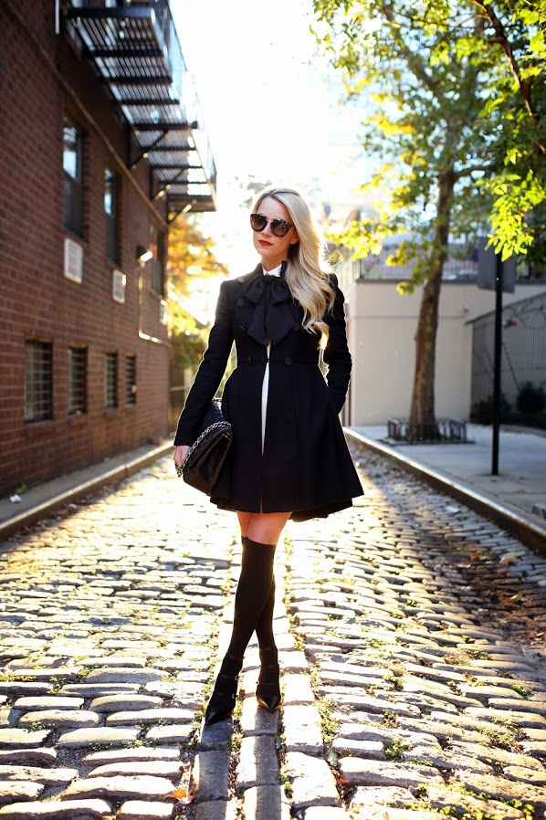 Blair Eadie is wearing a black jacket and skirt from Alice + Olivia, white top from ALC, black bow and knee high socks from Asos, shoes from Gianvito Rossi and the bag is from Chanel