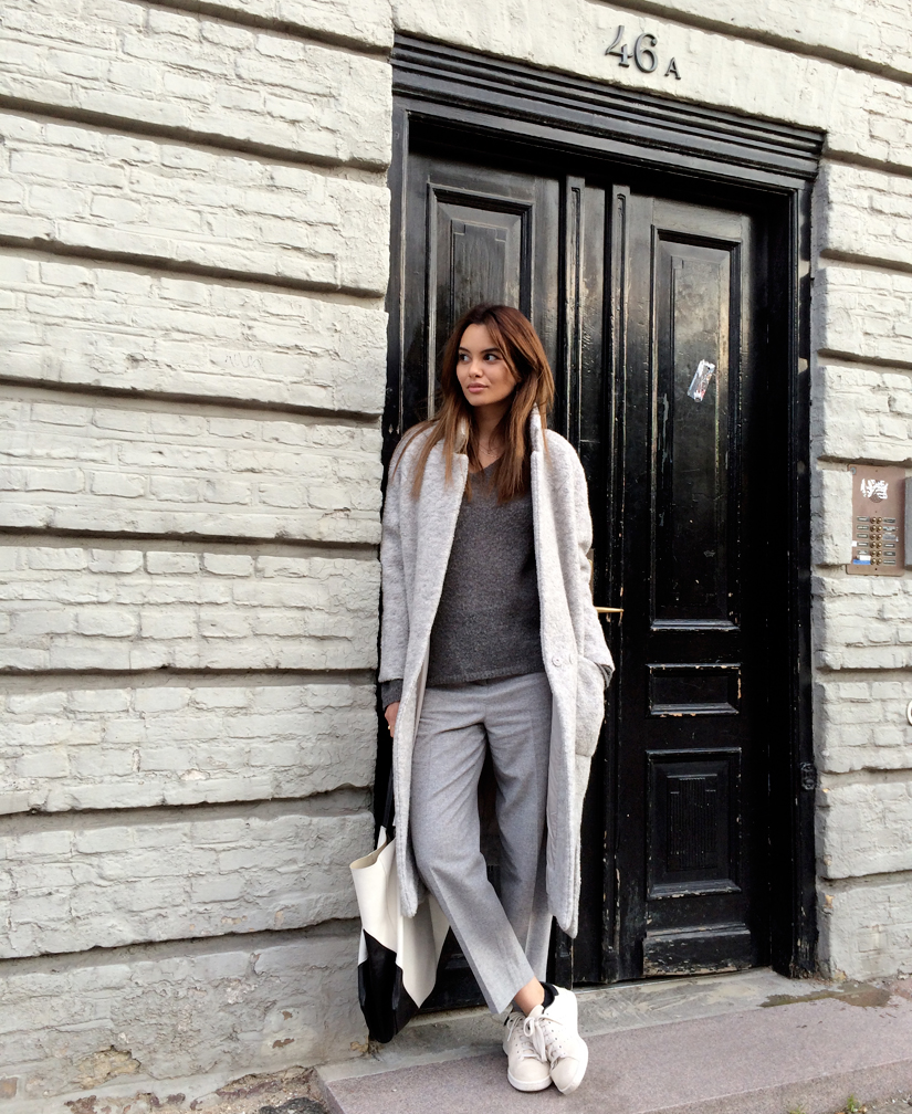 Funda Christophersen is wearing a grey long coat from Ganni, jumper from Moliin, trousers from Cos, bag from Celine and the shoes are from Adidas