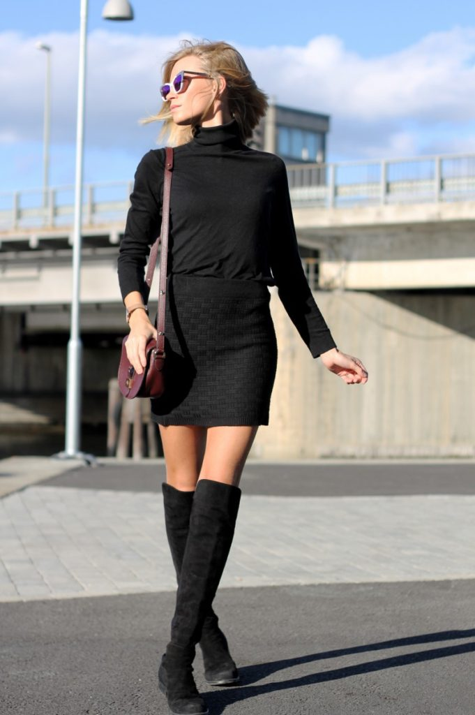 Tine Andrea is wearing a black textured skirt, black turtleneck from H&M, thigh high boots from Stuart Weitzman, bag from Mulberry and sunglasses from Karen Walker