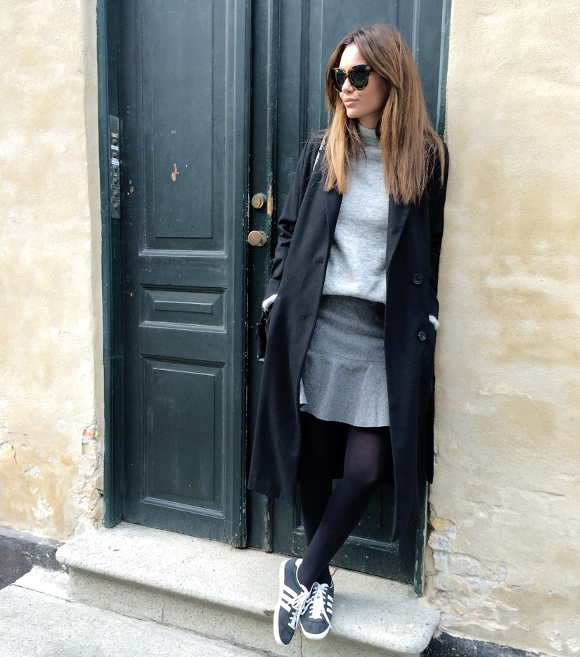 Funda Christophersen is wearing a long duster coat from Won Hundred, grey turtleneck from Gestuz, skirt from Second Female and sneakers from Adidas