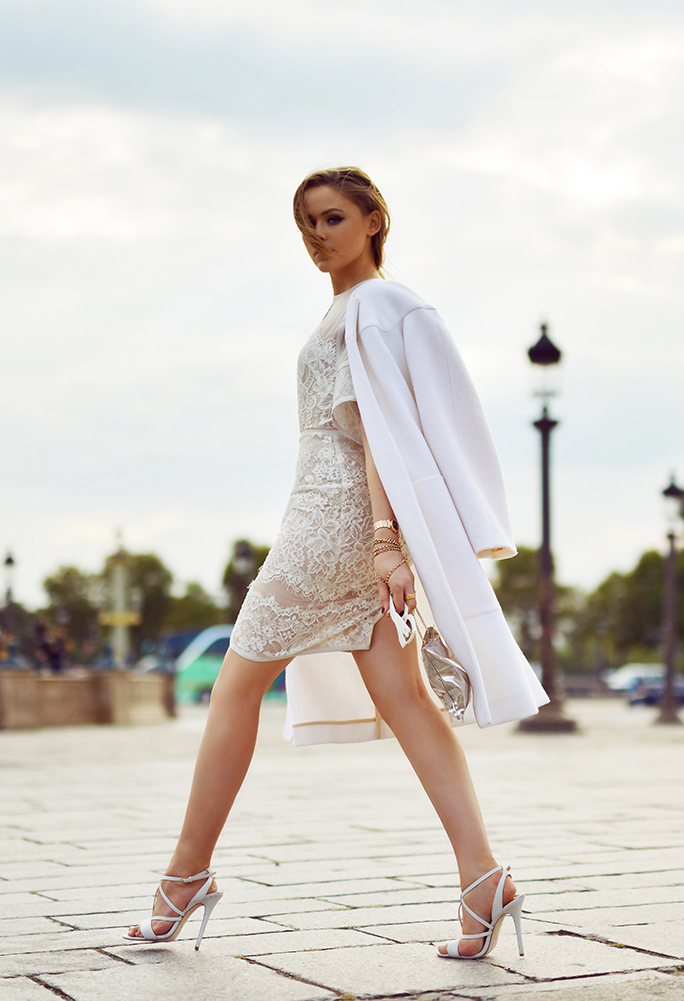 Kristina Bazan is wearing a white lace dress from and matching shoes from Elie Saab and the coat is from Chloé