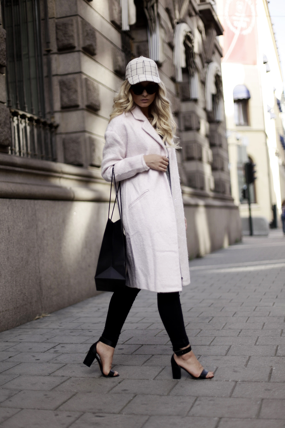 Marie Wolla is wearing a pink mohair coat from Only, plaid cap and grey T-Shirt from Monki, black jeans from Dr. Denim, shoes from Nelly and sunglasses from Celine