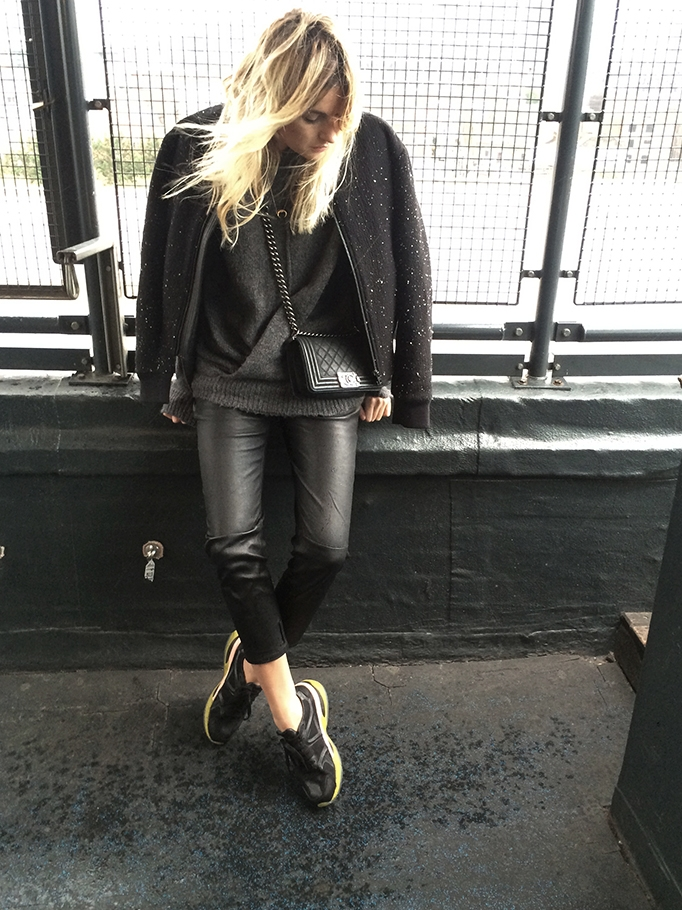 Camille Charriere is wearing a black bomber jacket from Rag & Bone, grey sweater from Isabel Marant, black leather trousers from Guess, sneakers from Puma and the bag is from Chanel