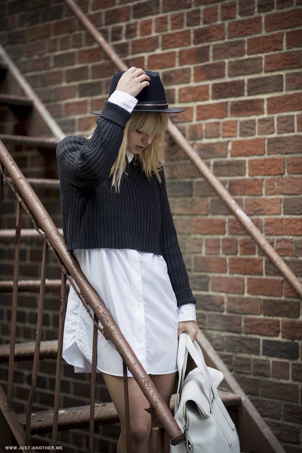 Lisa Dengler is wearing a white oversized shirt dress from Mads Noergaard, dark blue cropped knit top from Weekday and the hat is from Zara