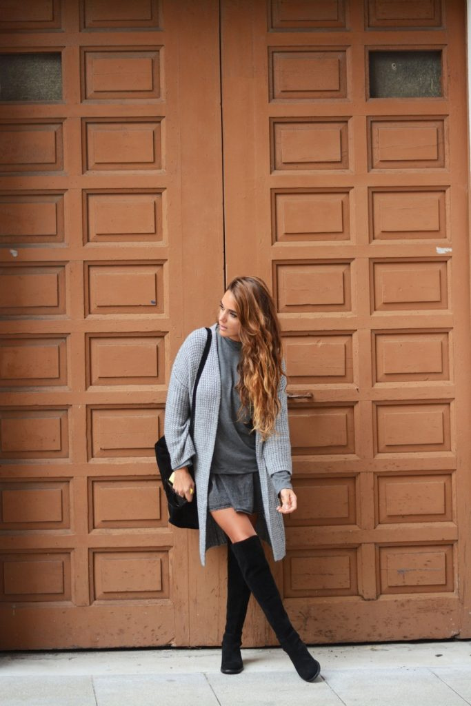 Stella Wants To Die is wearing a grey midi cardigan and T-shirt from Stradivarius, tall boots and a dress from H&M