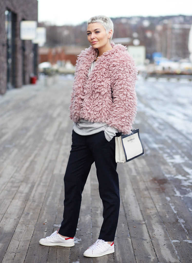 Marie Ullevoldsater is wearing a pink H&M fur coat, black Mq pants and Stan Smith Adidas sneakers