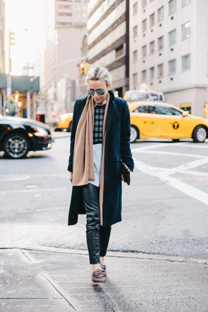 Jacey Duprie is wearing a pinstriped coat from Zara, plaid sweater from ALC, white silk shirt from Maje, clutch from Clare Vivier, trousers from Helmut Lang, loafers from J. Crew and the scar is from Cos
