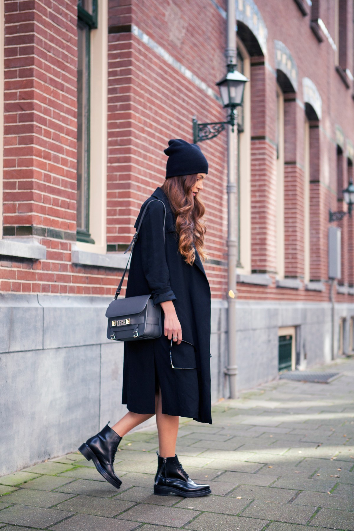 Negin Mirsalehi is wearing a long black flowy coat from Zara and the beanie is from Urban Outfitters