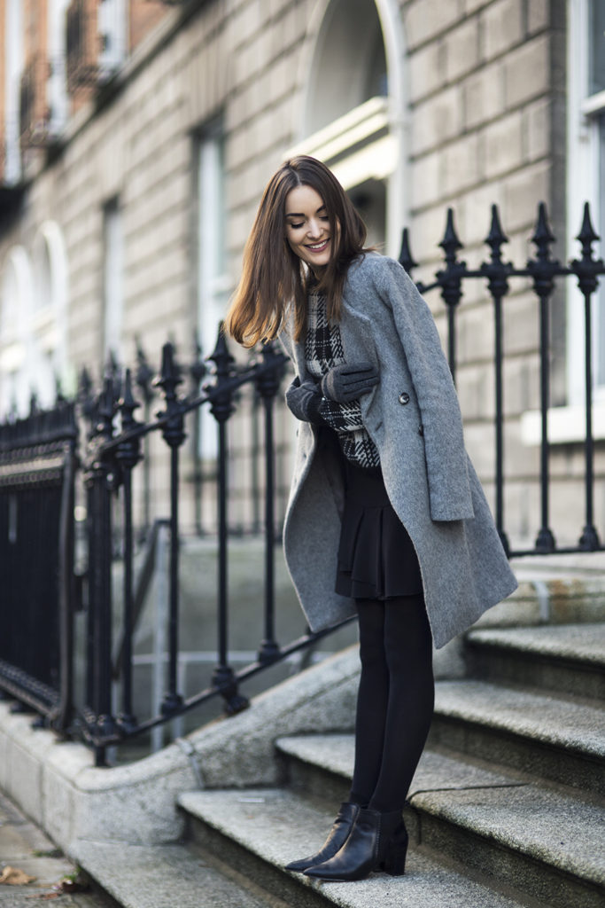 Anouska Proetta Branson is wearing a grey midi coat, tartan sweater and black skirt from Benetton and the shoes are from Reiss