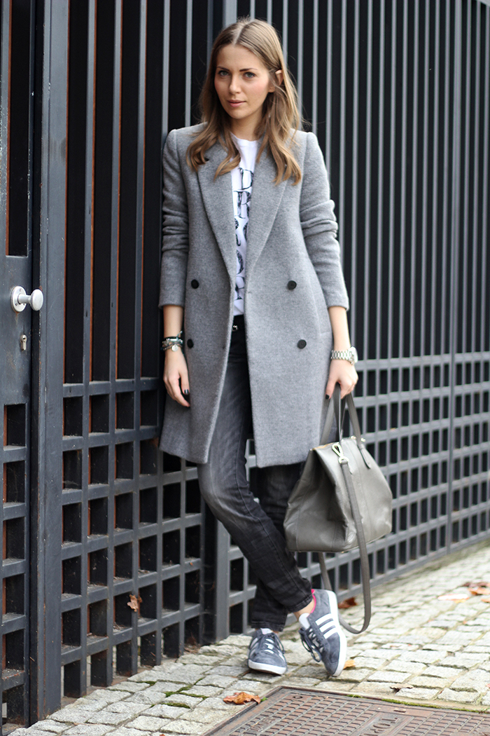 Vanja Milicevic is wearing sneakers from Adidas, faded jeans, T-Shirt and structured grey coat from Zara, and the bag is from DKNY