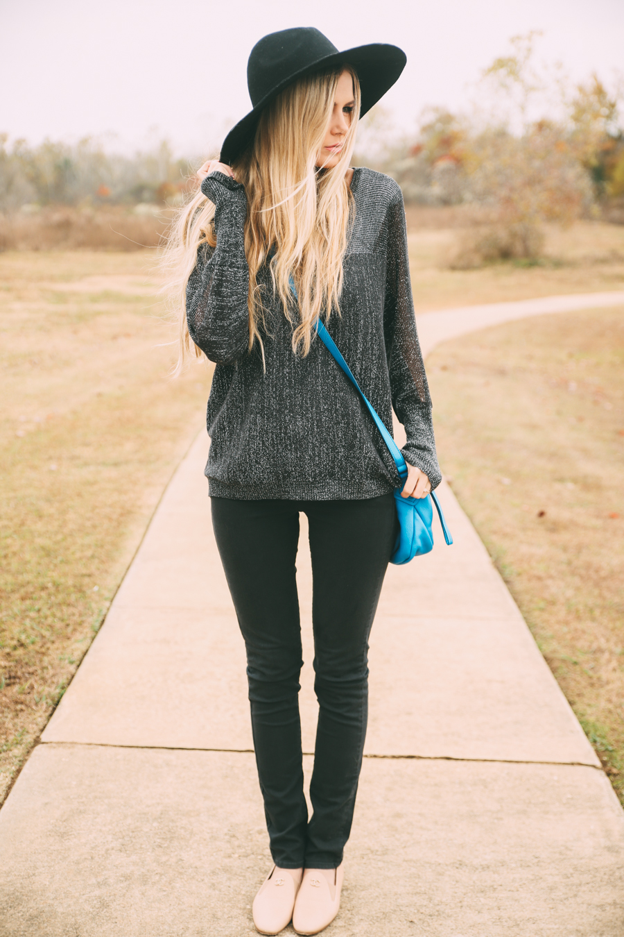 Amber Fillerup Clark in her grey sweater and black jeans from Ruche, loafers from Chanel, bag from Marc Jacobs and the hat is from Forever 21