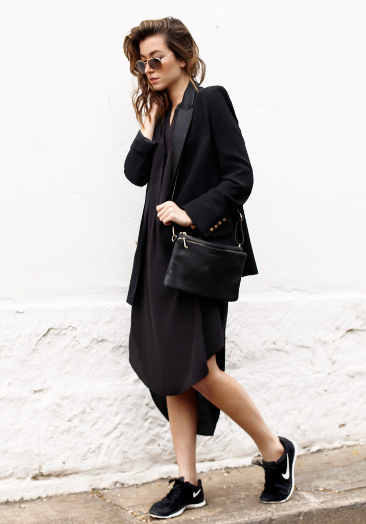 Carmen Hamilton is wearing a black dress and bag from Sportscraft, black blazer from Mango, sneakers from Nike and the sunglasses are from Tom Ford