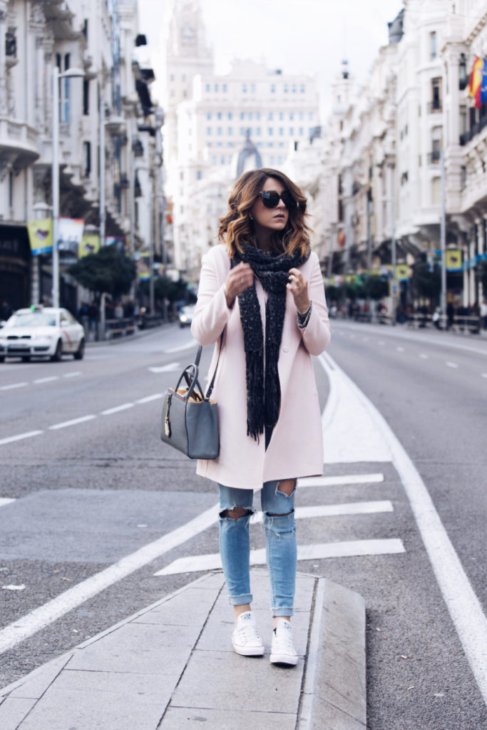 Nicoletta Reggio is wearing a pink coat from Prada, scarf and ripped jeans from Zara, shoes from Converse and the bag is from Fendi