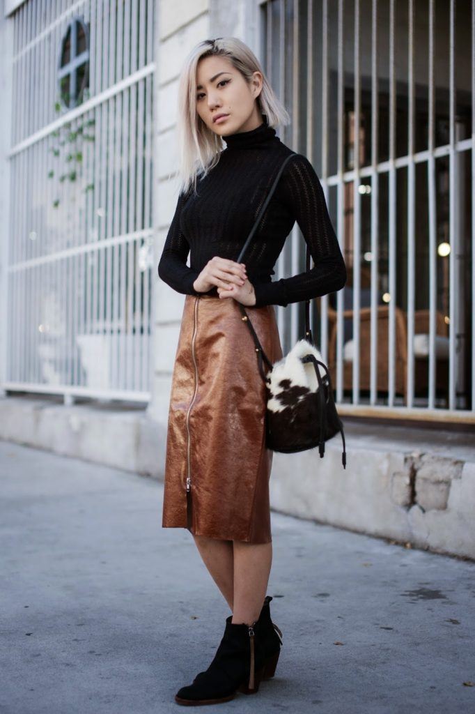 Eugenie Grey is wearing a black top and bag from DailyLook, brown leather skirt from Kahlo and the ankle boots are from Acne