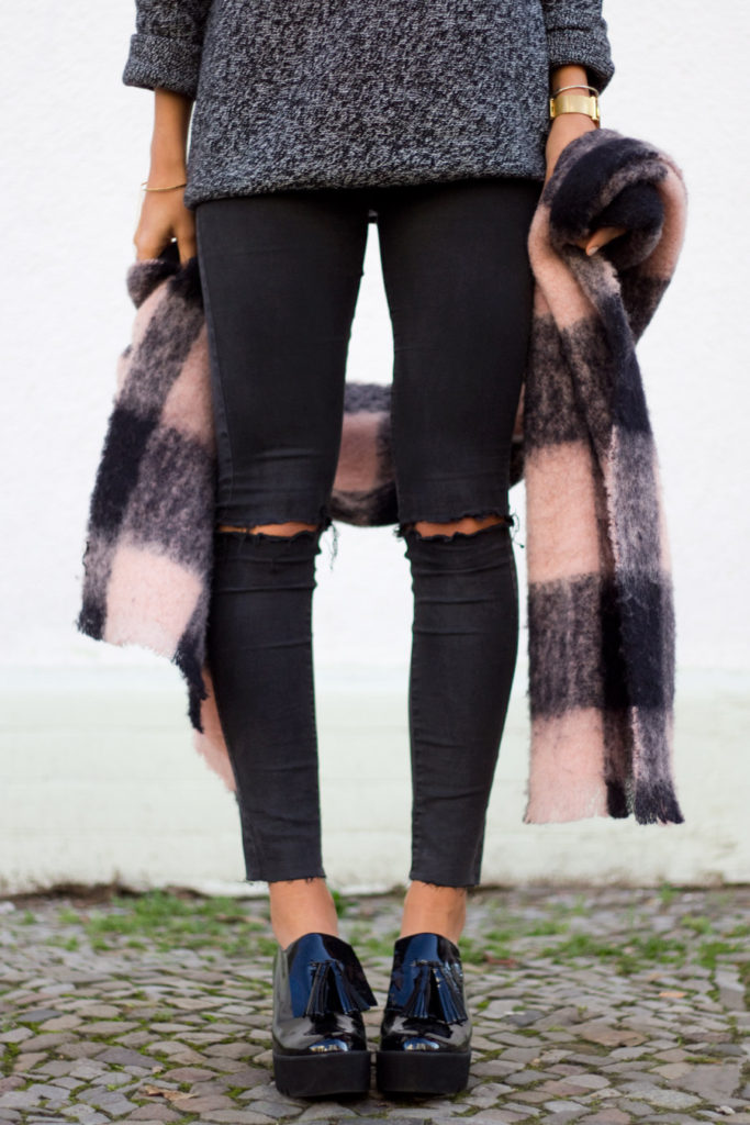 Kayla Seah is wearing a low rise black jeans with ripped knees from Asos