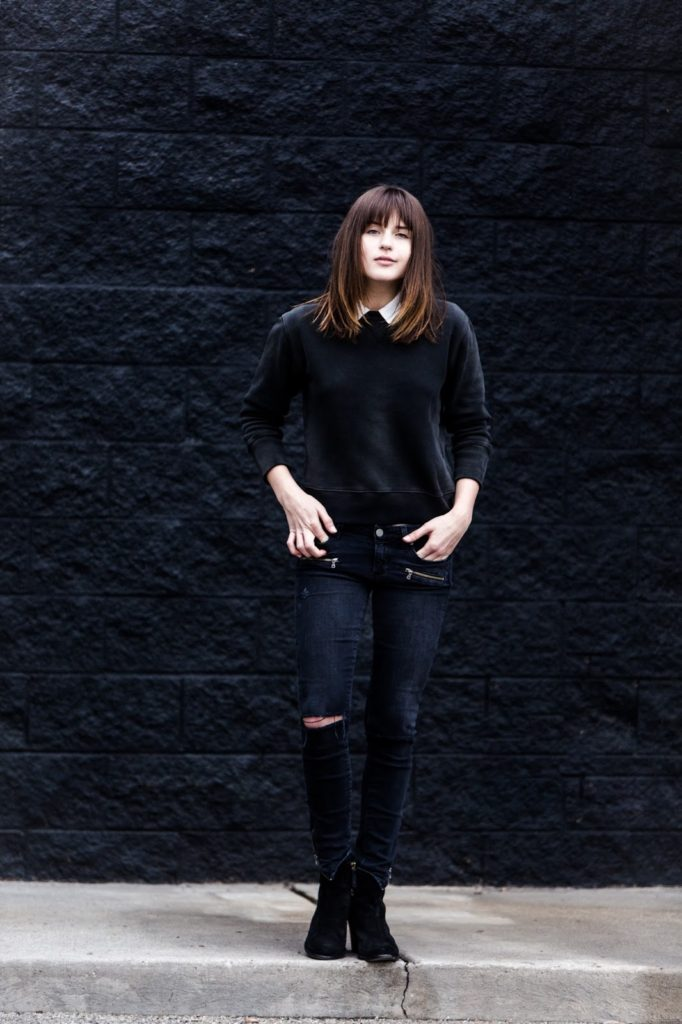 Rima Vaidila is wearing a black ripped skinny jeans from Paige Denim