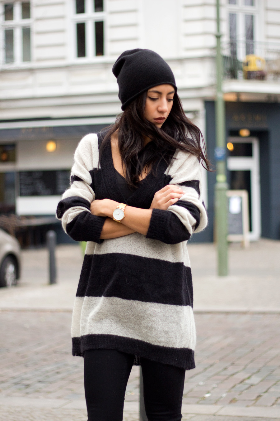 Deep V Neck Trend: Kayla Seah is wearing a black and white striped deep V neck sweater from Carin Wester