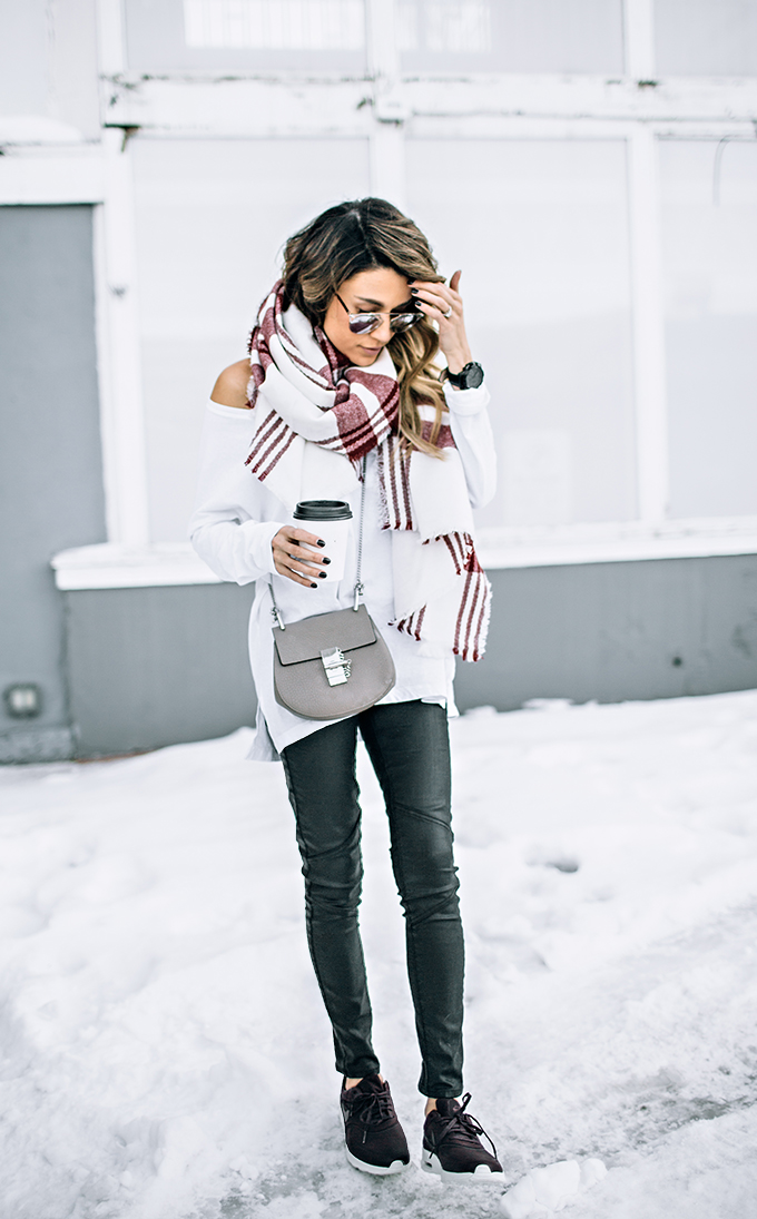 Wear the plaid trend on your oversized scarf to both keep it casual and brighten up your outfit. This white and red design worn by Christine Andrew makes a great addition to an otherwise simple outfit. Top: Old Navy, Trousers: Nordstrom, Scarf: Ily Couture.