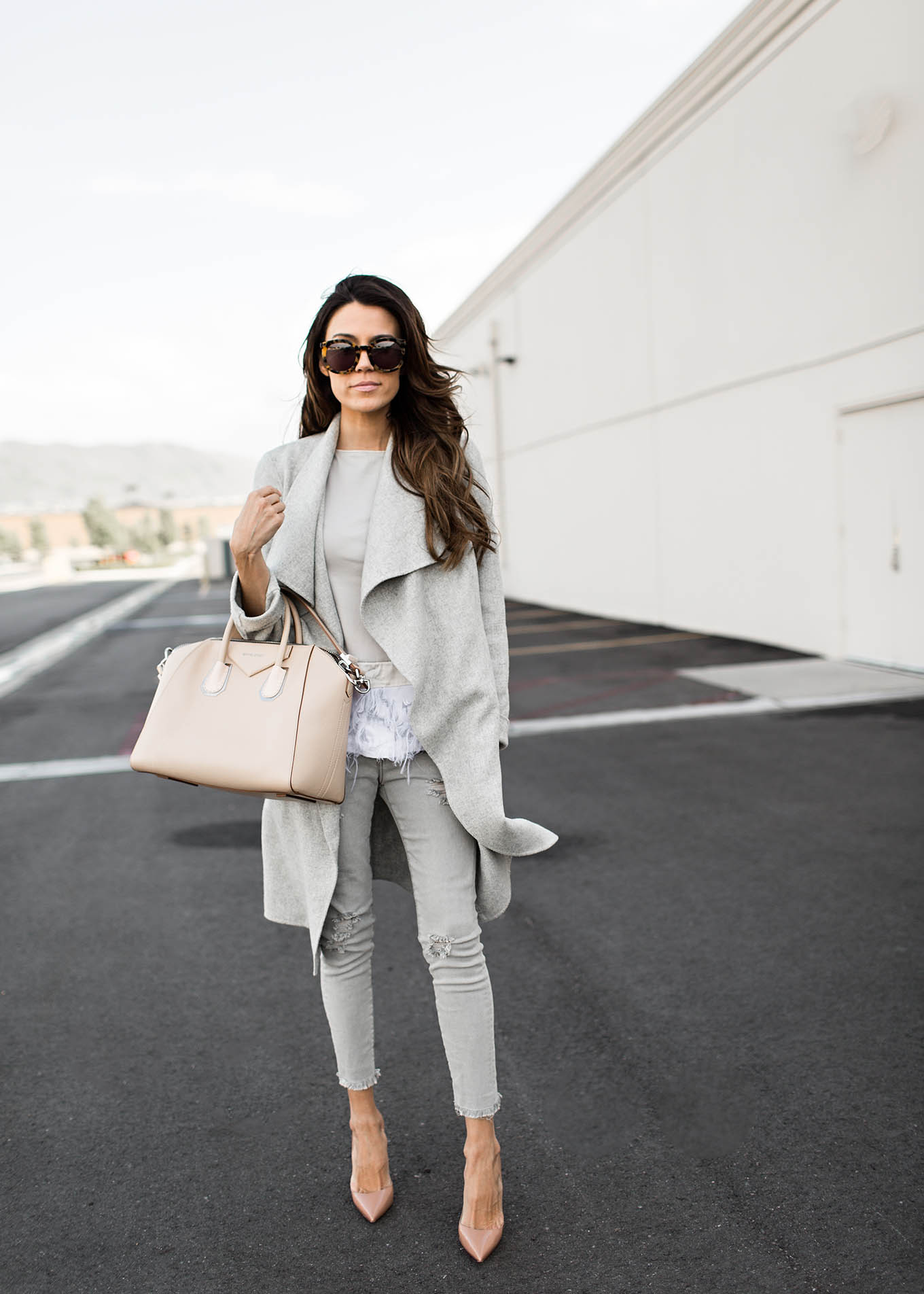Christine Andrew is looking effortlessly stylish in this grey on grey ensemble consisting of a wrap coat, a pair of grey skinnies and a cute fringe detailed top. This colour scheme is ideal for everyday neutral wear! Top/Jeans: Nordstrom.