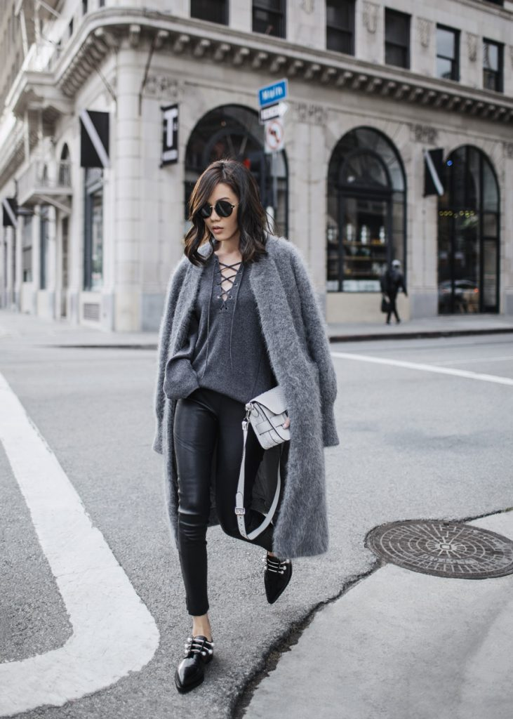 Jenny Tsang is absolutely rocking this authentic grey layering trend!  By pairing a flowing blanket coat with a tie-front tee and leather leggings, Jenny has achieved the perfect contrast between tight and loose! We adore this look.  Coat: Tsang, Sweater: Vince, Trousers: Blesse'd Are the Meek.