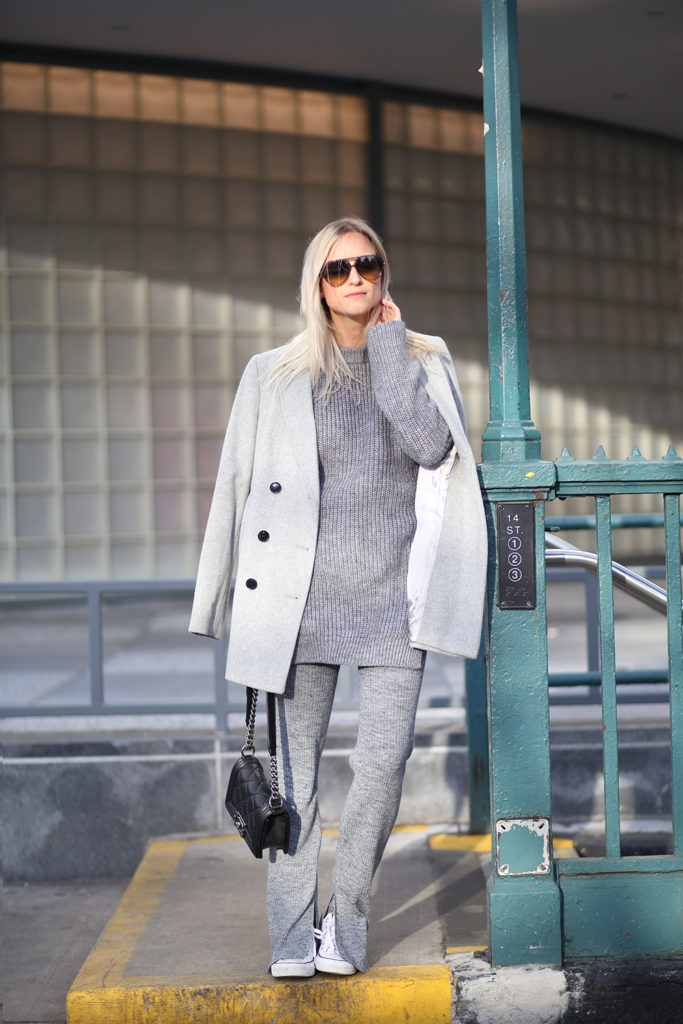 Charlotte Groeneveld is wearing a pale grey coat from Jaeger, grey knit jumper and trousers from Zara, bag from Chanel and Converse trainers