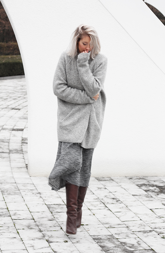 Joyce Croonen is wearing grey on grey, jumper from Acne, skirt from Monki and the brown boots are from H&M