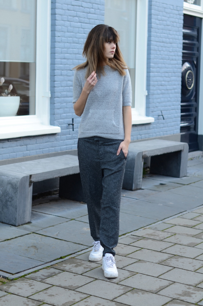 Lovely by Lucy is wearing a grey knitted top from Asos, grey trousers from Selected and the white trainers are from Nike