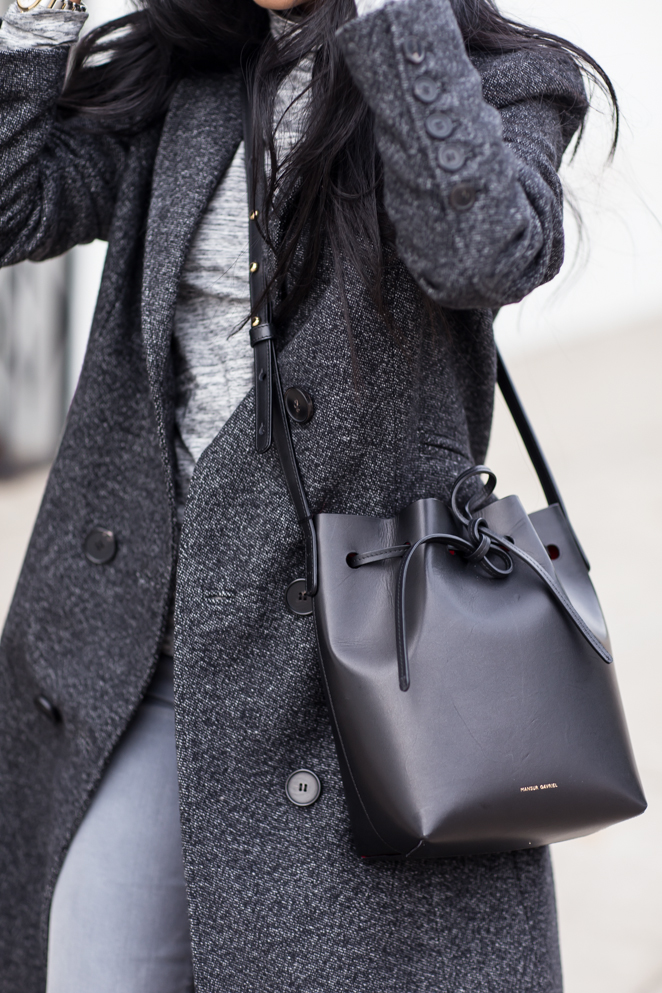 Sheryl Luke is wearing a charcoal coal from 7 For All Mankind, grey jeans from Joes Jeans, sweater from J Crew and the bag is from Mansur Gavriel