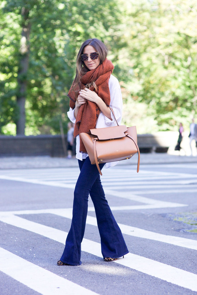 Arielle Nachami wears an oversized rust coloured scarf with ultra cool denim flares and leopard print heels.   Jeans: L'Agence, Shirt: Elizabeth and James, Scarf: Zara, Bag: Celine, Sunglasses: Miu Miu.