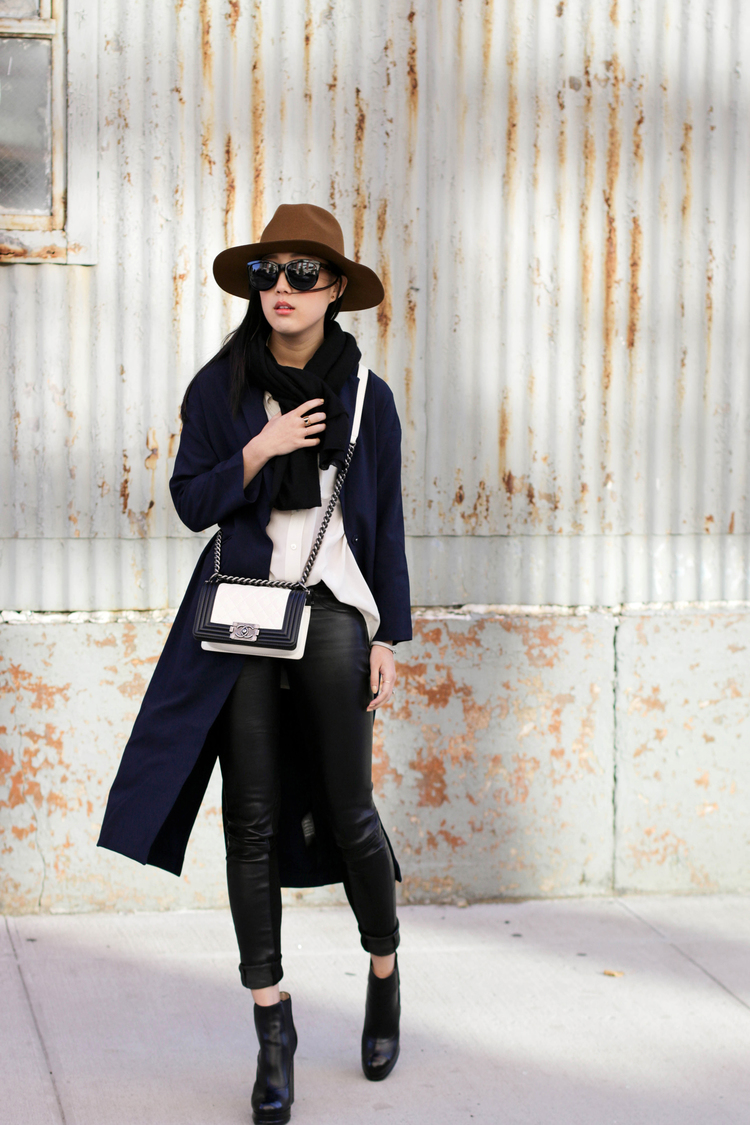 Erica Choi is wearing a white top from Equipment, black leather jeans from Rag & Bone, dark blue duster from Asos, hat from Janessa Leone and the shoes and bag is from Chanel