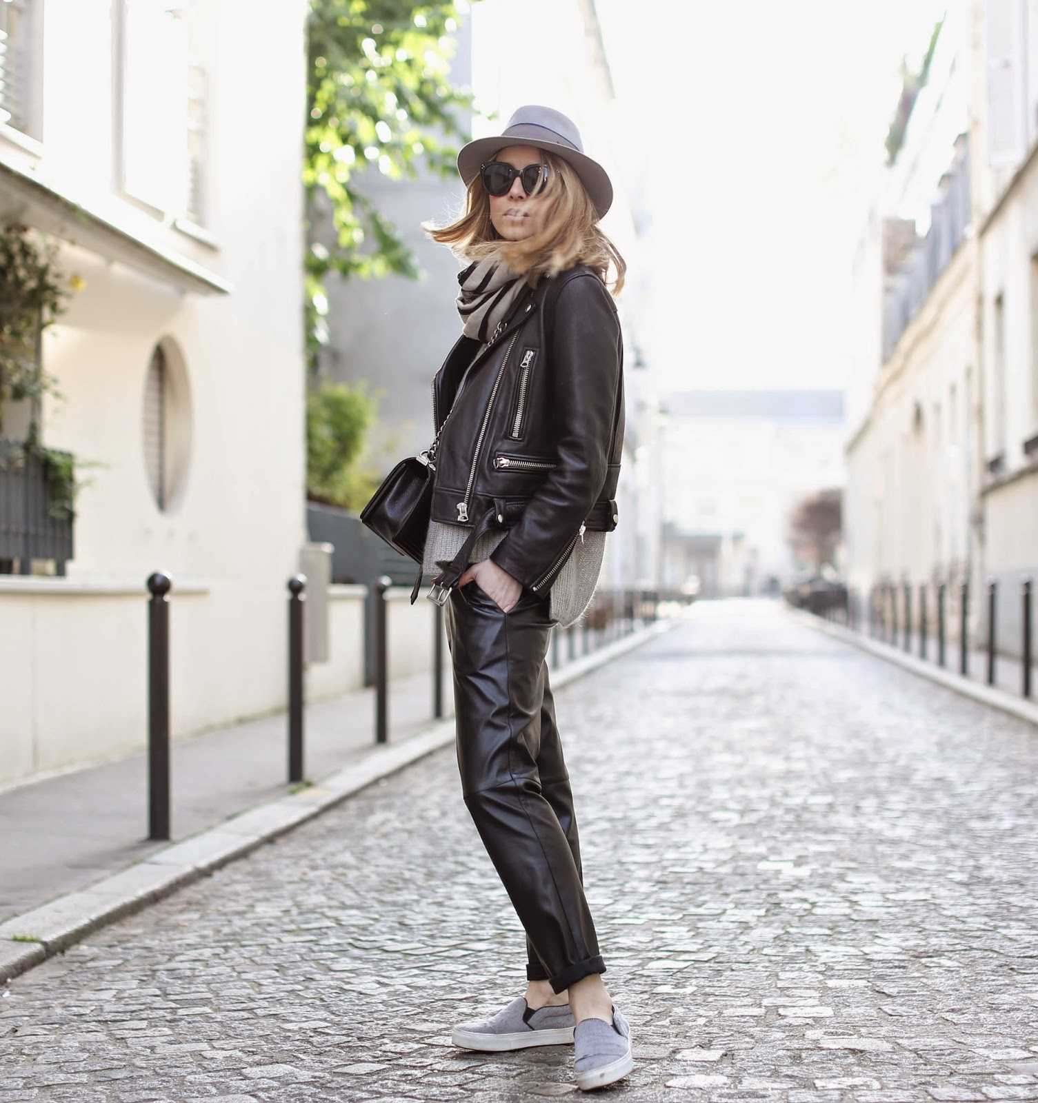 Caroline Louis is wearing a biker jacket from Acne, leather trousers from L'Art du Basic, grey scarf from Hermès and matching slip-ons from Céline and the hat is from Maison Michel