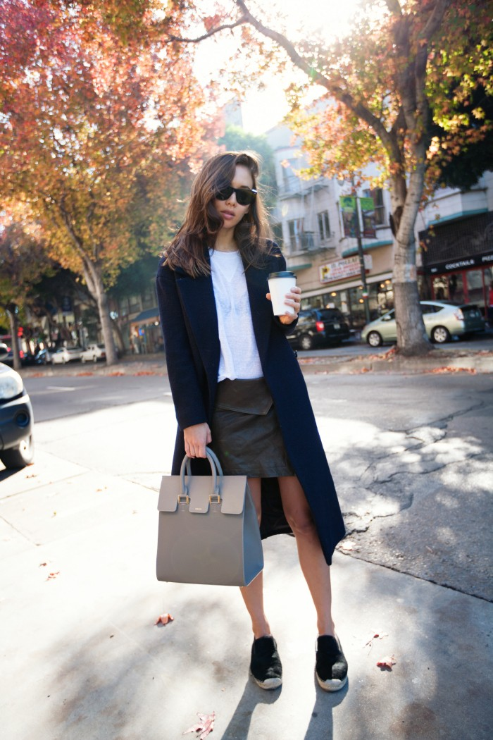 Rumi Neeley is wearing a dark blue mohair jacket from Cos, T-shirt from Are You Am I, olive leather skirt from Isabel Marant, khaki bag from Mezzi Cosima and the espadrilles are from Céline