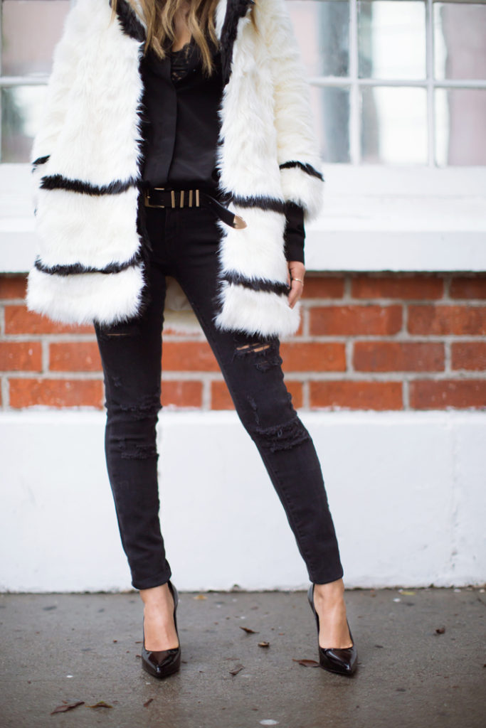 Aimee Song is wearing a black and white faux fur jacket from H&M, black ultra skinny jeans from Paige Denim, black silk blouse from Anine Bing and shoes from Saint Laurent