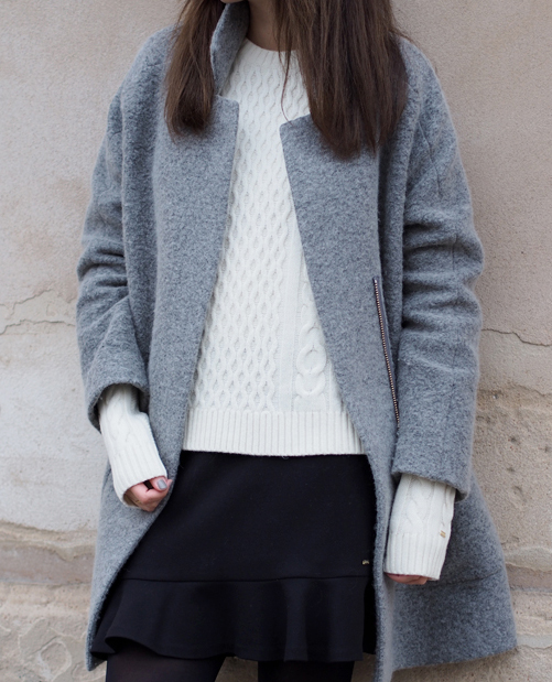 Funda Christophersen is wearing a grey coat from Sand and white knit sweater and dark blue skirt from Tommy Hilfiger