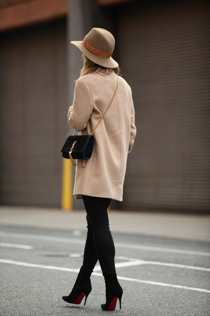 Helena Glazer is wearing a camel coloured coat from Theory, black jeans from Current/Elliott, hat from Preston & Olivia, boots from Christian Loboutin and the bag is from Saint Laurent
