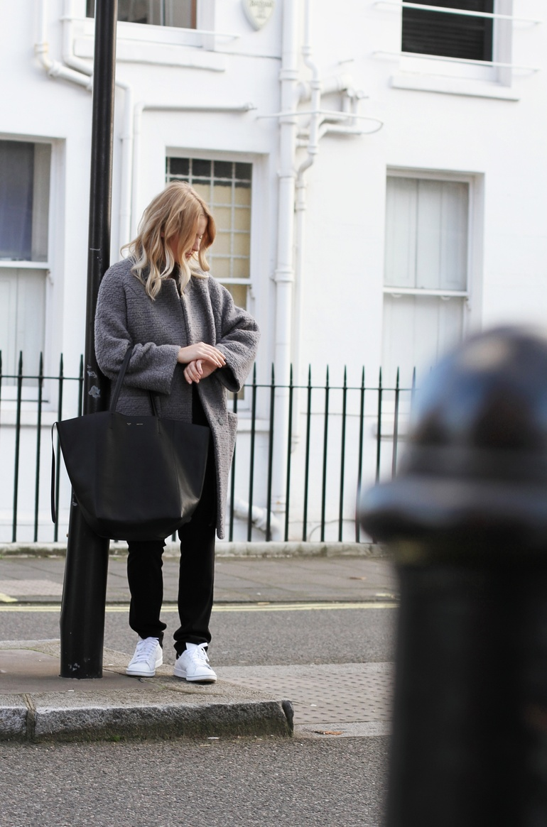Mirjam Flatau is wearing a grey wool coat and black trousers from Ganni, a bag from Celine and the shoes are from Adidas