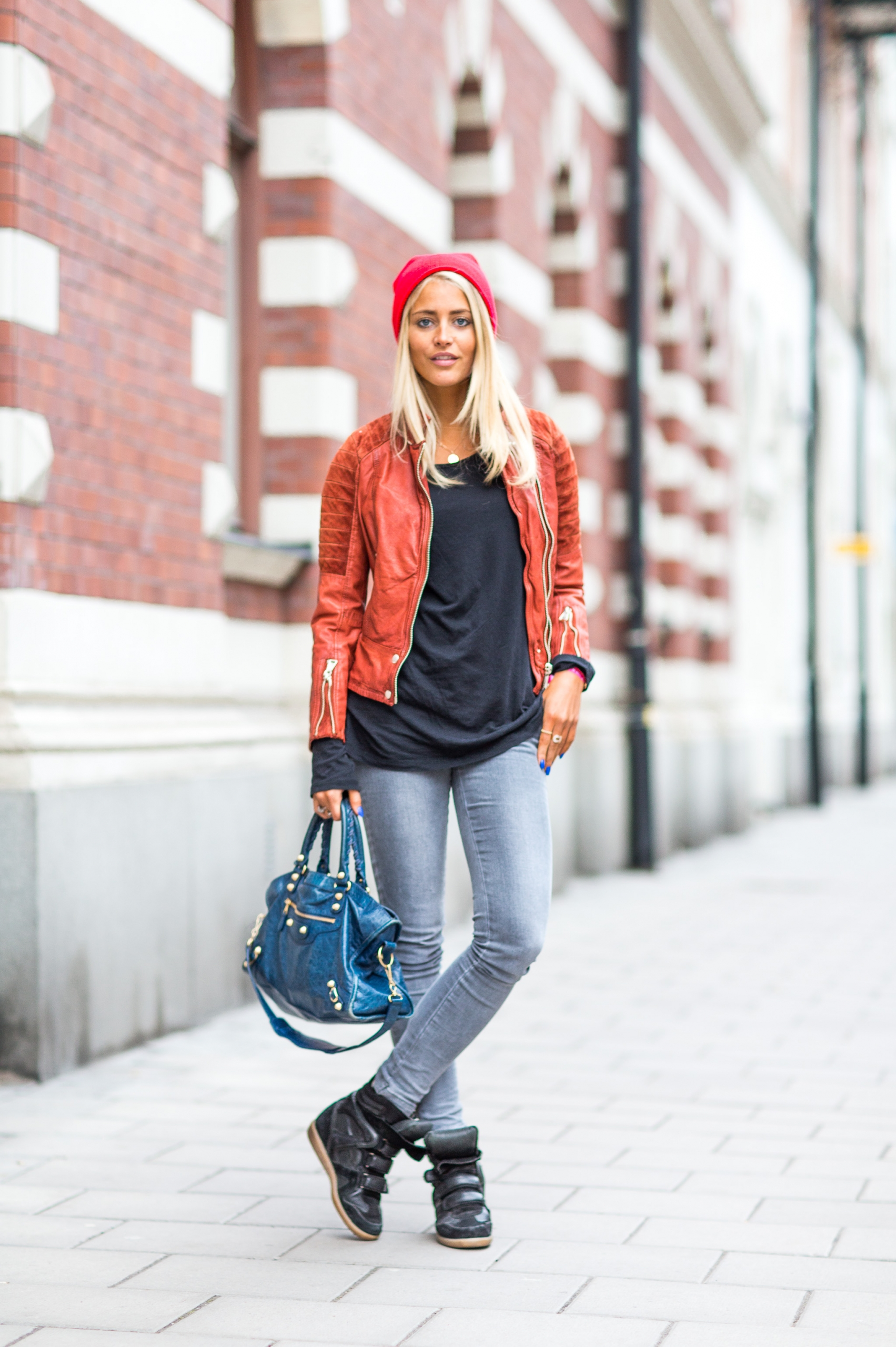 Janni Deler is wearing a red hat from River Island, terracotta leather jacket from Jofama, long sleeved black top from H&M, bag from Balenciaga and shoes from Isabel Marant