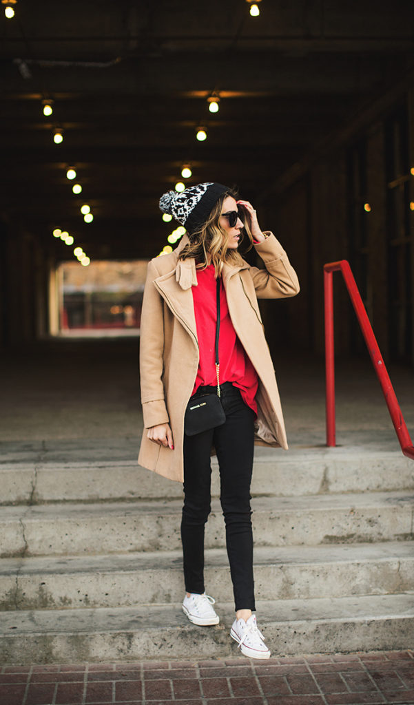 Christine Andrew is wearing a camel coat from Ily Couture, long sleeved red top and beanie from Gap, black coated skinny jeans from Joe's Denim and the mini bag is from Michael Kors