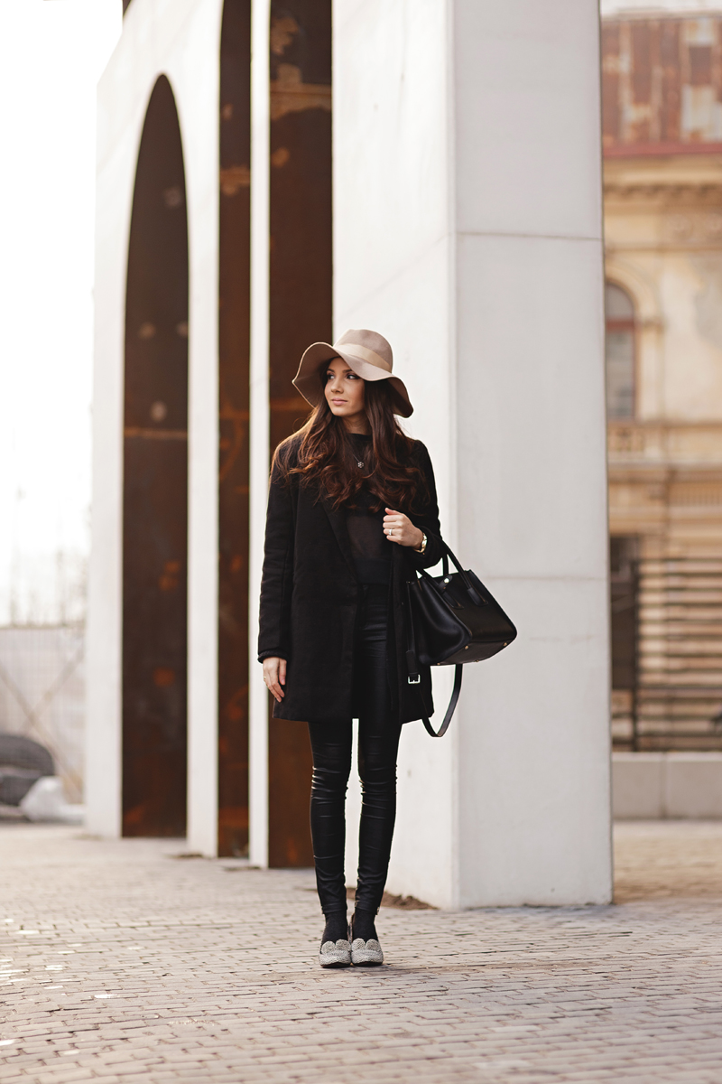 Larisa Costea is wearing a beige floppy hat from Punsunmaill, black coat from SheInside, top from MissGuided, bag from Jadu, leggings from Little Mistress and shoes from Chie Mihara