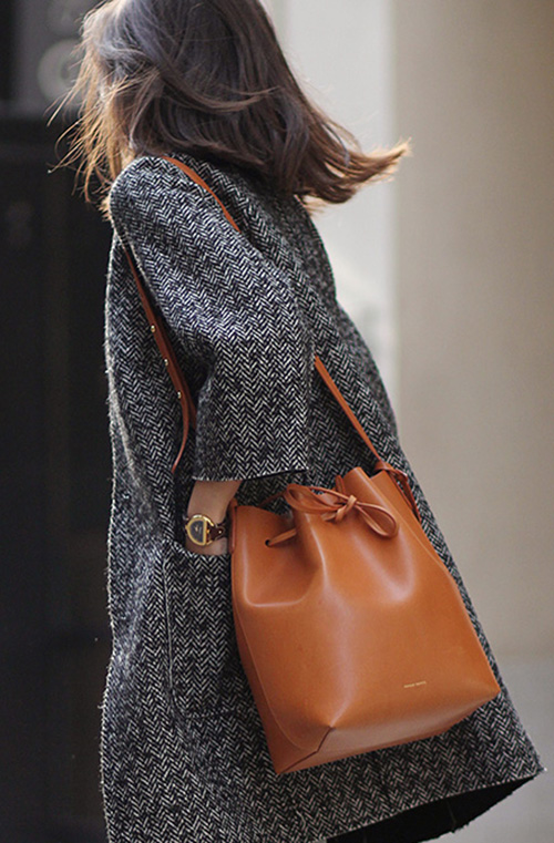 Adriana Gastélum is wearing a brown bucket bag from Mansur Gavriel
