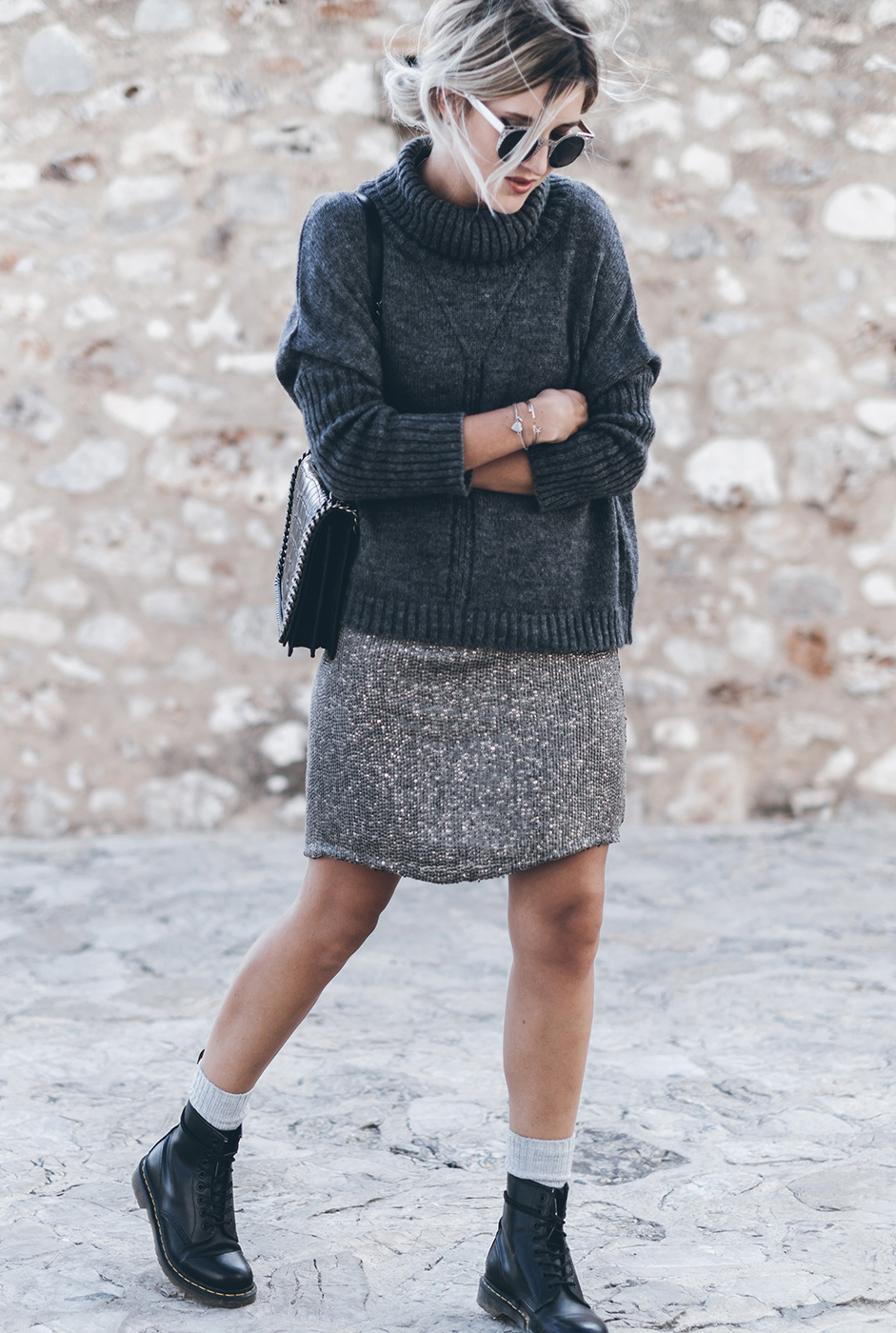Wear your grey knit sweater with a grey skirt, grey socks and a pair of Dr. Martens. Via Jacqueline Mikuta. Sweater: VILA, Skirt – Anncha, Boots: Dr.Martens, Bag: Zara, Sunglasses: ZeroUV