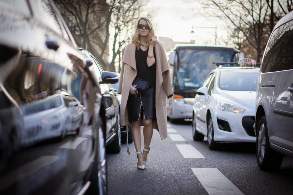 Caroline Louis is wearing an oversized Zara camel coat with a black leather Jupe skirt and a black Chanel clutch