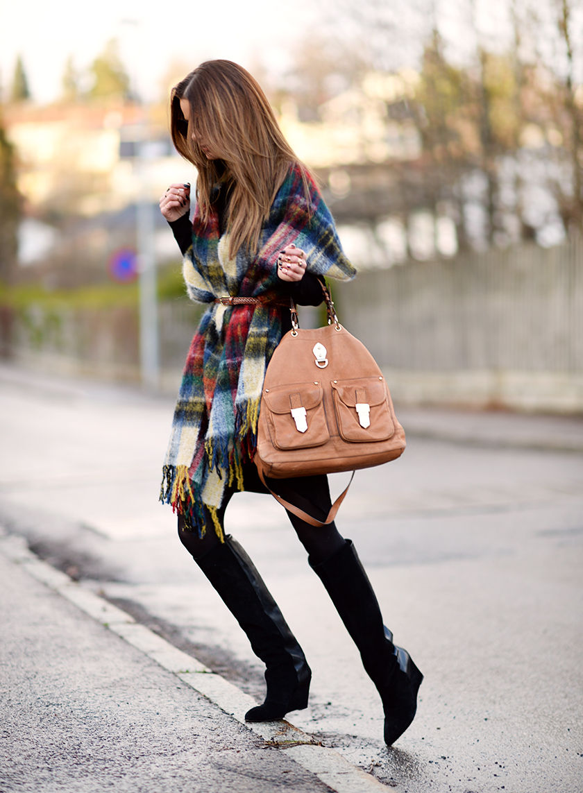 Annette Haga is wearing a multicoloured plaid oversized scarf from Holzweiler styled with a belt